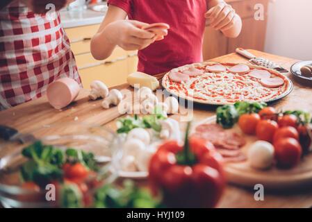 Madre e figlia preparare la pizza in cucina Foto Stock