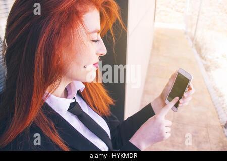 Giovani redhead business donna lavora con il suo smartphone Foto Stock