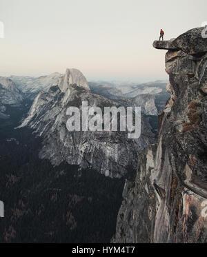 Un intrepido escursionista è in piedi su una roccia a strapiombo godendo della vista verso il famoso Half Dome al punto ghiacciaio nel Parco Nazionale di Yosemite in California
