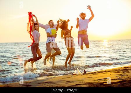 Un gruppo di giovani felici hanno balli sulla spiaggia il bellissimo tramonto estivo