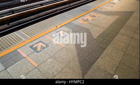 Segno di freccia sulla piattaforma ferroviario alla stazione ferroviaria Foto Stock