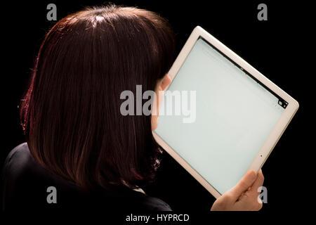 Donna che guarda l'iPad Pro tenuto in mano contro lo sfondo nero Foto Stock