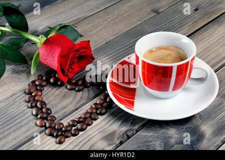aromatico-stile-italiano-caffe-servito-in-una-bella-tazza-di-rosso-su-di-un-tavolo-di-legno-vecchio-adornata-con-una-rosa-rossa-e-i-chicchi-di-caffe-hyr1d2.jpg