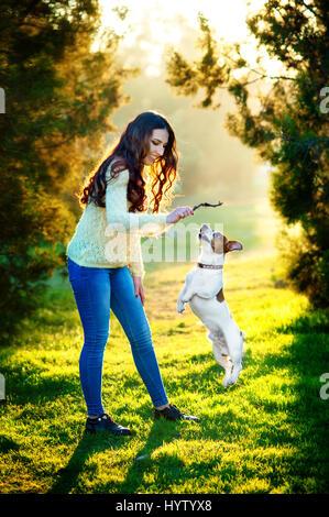 Giovane donna a piedi con un cane la riproduzione di formazione, jumping cane. Jack Russell Terrier Foto Stock