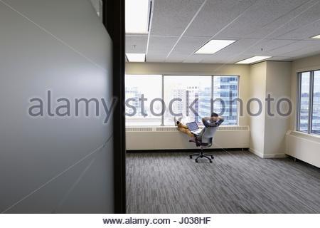Imprenditore rilassato con laptop e piedi fino a vuoto nuovo ufficio Foto Stock