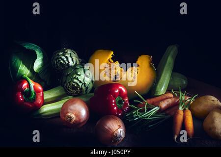Colorata di verdure fresche su sfondo nero. Carote, cavolo, zucca, cipolle e zucchine, patate, pomodori, carciofi e pepe rosso. Vintage Sty
