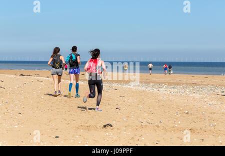 Gruppo reali di giovani uomini e donne correre sulla spiaggia a Margate, Kent, Inghilterra Foto Stock