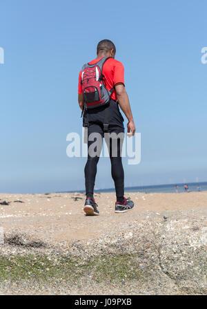 I giovani adulti l'uomo corre sulla spiaggia a Margate, Kent, Inghilterra Foto Stock