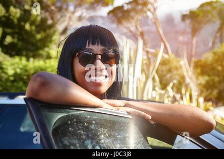 Ritratto di giovane donna in piedi accanto a AUTO, poggiando sulla portiera aperta Foto Stock