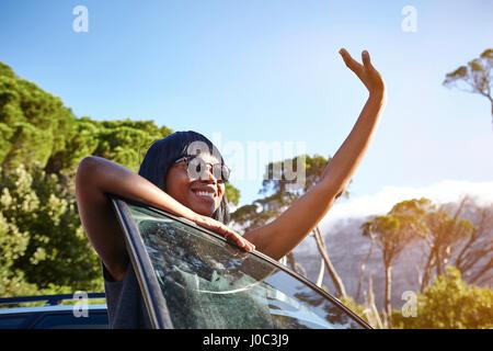 Ritratto di giovane donna in piedi accanto a AUTO, poggiando sulla portiera aperta, sventolando Foto Stock