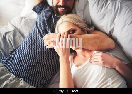 Giovane rilassante sul letto, ingannare circa Foto Stock