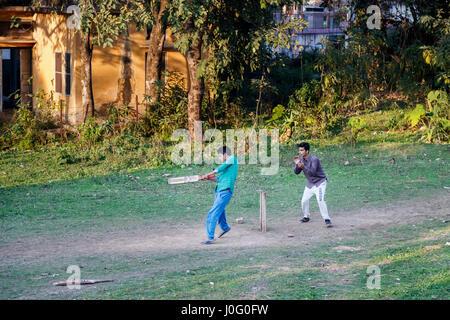 Due locali ragazzi indiani divertirsi giocando una partita di cricket su un polveroso pitch in Pragpur, un villaggio del patrimonio culturale nel quartiere Kagra, Himachal Pradesh, India
