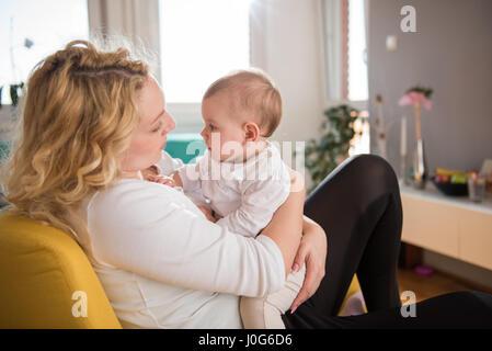 La madre tiene il Bambino fra le braccia e seduti in poltrona di colore giallo