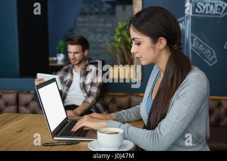 Giovane donna utilizzando computer portatile mentre un caffè in café Foto Stock