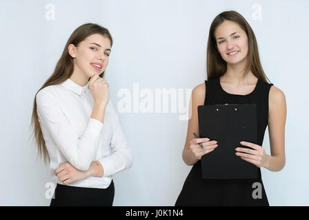 Due business woman standing con alle loro spalle insieme Foto Stock