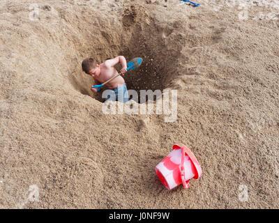 Ragazzo giovane scava grande buco con benna e il capocorda a forcella sull UKbeach Foto Stock