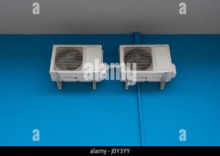 Il condizionatore d'aria unità di condensazione sulla parete blu all'esterno dell'edificio. Foto Stock