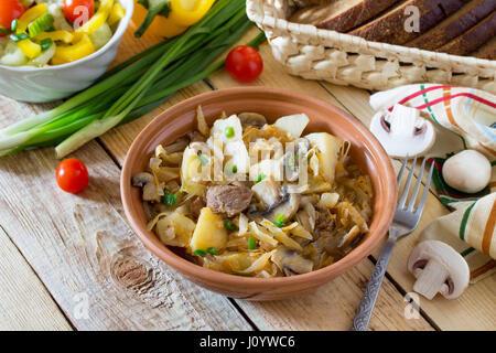 Cavolo stufati con funghi, funghi porcini e sugo di pomodoro con verdure fresche su un tavolo di legno. Foto Stock