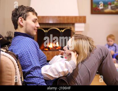 Famiglia riscaldata dal camino seduta sul lettino Foto Stock