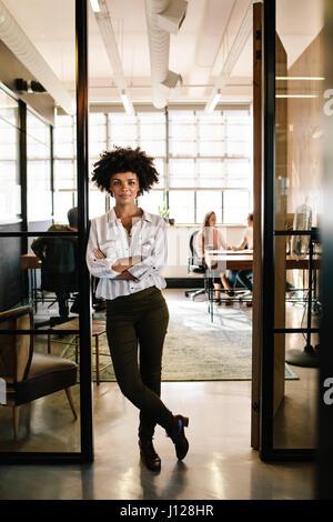 A piena lunghezza Ritratto di fiducioso giovane donna in piedi nella porta di office con le braccia incrociate. Foto Stock