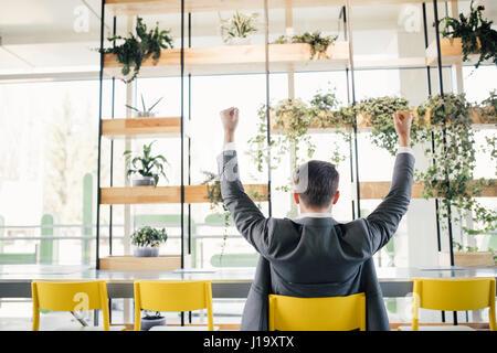 Business di successo di uomo felice sorriso tenere il gesto del pugno di vista dal retro, bel giovane imprenditore Foto Stock