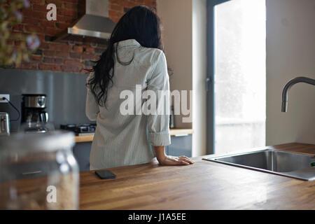 Bella giovane donna nella sua cucina Foto Stock