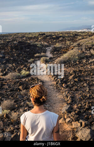 Caucasian donna in piedi sul sentiero attraverso le rocce