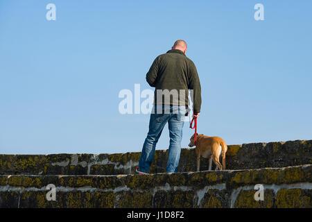 L uomo si prende il suo cane per una passeggiata lungo il molo a Charlestown Harbour, Cornwall, Regno Unito 18/04/2017
