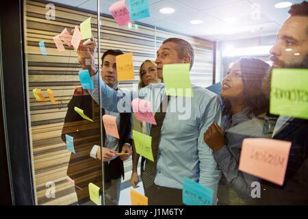 Gruppo misto di gente di affari avente un incontro permanente presso l'ufficio. Utilizzando gli adesivi e poster Foto Stock