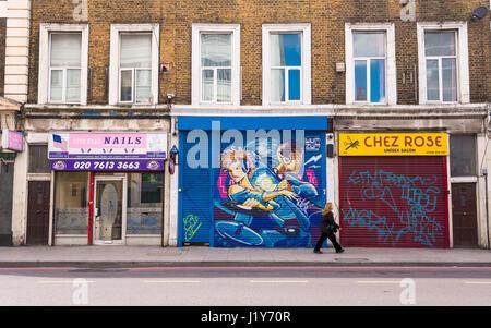Donna che cammina in un tradizionale UK street con una manicure, un barbiere unisex e un negozio chiuso con otturatore Foto Stock