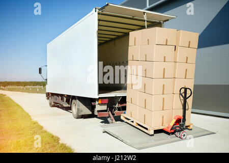 Carrello di trasporto di merci imballate in scatole dal magazzino Foto Stock