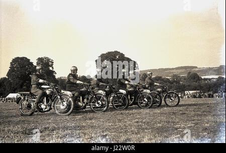 Degli anni Cinquanta, storico, un motociclo display o stunt team line up in un campo per eseguire presso la contea Foto Stock