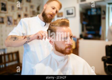 Ricezione maschio capelli barba di trattamento in un barbiere Foto Stock