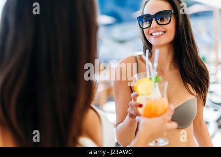 Femmina allegro gli amici a bere un cocktail in estate e sorridente Foto Stock