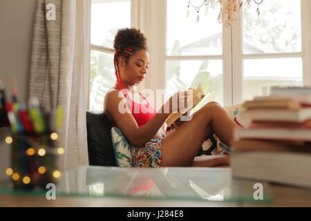 Felice studentessa la lettura del libro e seduto sul divano. Giovane africano donna americana rilassante, nero ragazza Foto Stock