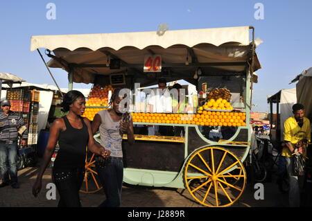Le donne senegalesi a piedi da un succo di arancia fornitore nel Djema El Fna a Marrakech. Foto Stock