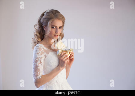 Sposa abiti da sposa tenendo un cioccolato Foto Stock