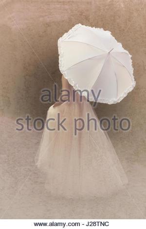 Vista posteriore della donna in abito rosa tenendo un ombrellone Foto Stock