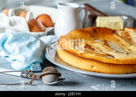 Crostata di frutta con pere sullo sfondo di ingredienti (uova, latte, burro). Foto Stock