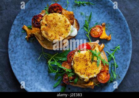 Cotto formaggi di capra su pane a lievitazione naturale con finferli e pomodorini Foto Stock