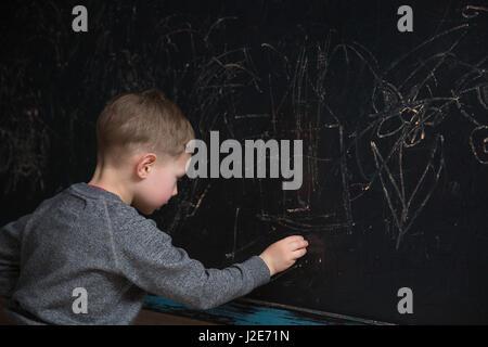 Vista posteriore dei maschi di scuola elementare studente scrive sulla lavagna Foto Stock