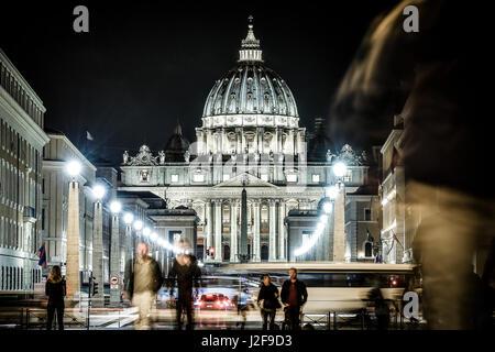 Vista illuminata Basilica di San Pietro, Via della Conciliazione e sentieri di luce delle vetture in Roma, Italia Foto Stock