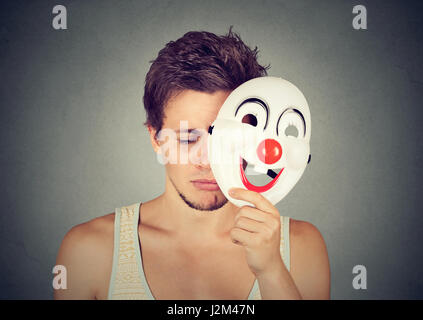 Giovane uomo triste decollare clown maschera isolata sul muro grigio Sfondo. Le emozioni umane Foto Stock