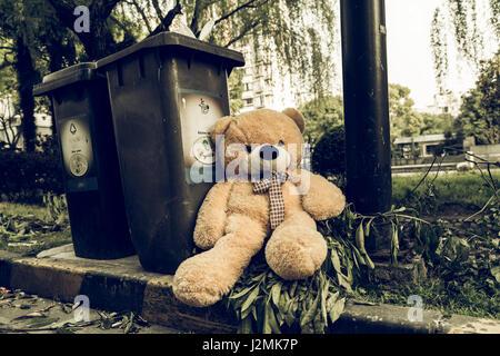 Il teddy-bear è stato buttare via seduto accanto a i rifiuti nel cestino Foto Stock