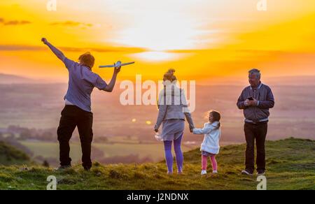 Famiglia amorevole giocando e gustando ottimi tempi su una collina vicino al tramonto nella campagna del Regno Unito. Trascorrere del tempo insieme.