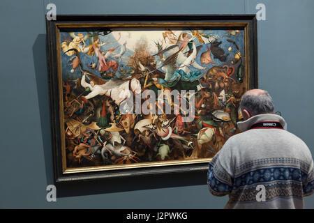 """Visitatore davanti al dipinto """"La caduta degli angeli ribelli' olandese da pittore rinascimentale Pieter Bruegel Foto Stock"""