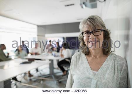 Ritratto sorridente imprenditrice a lavagna nella sala conferenza incontro Foto Stock