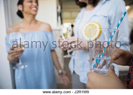 Le donne di bere vino bianco e limone acqua sul patio Foto Stock