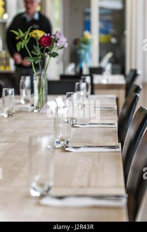 Bicchieri vuoti su un tavolo da pranzo nottolini posate pulite inutilizzati ristorante interno Foto Stock
