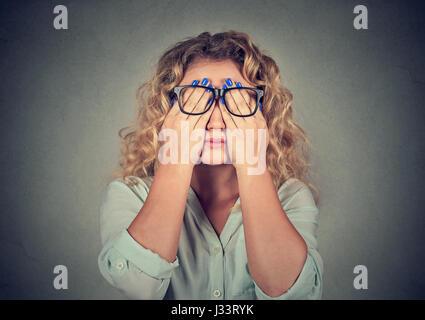 Closeup ritratto giovane donna in bicchieri che ricopre la faccia gli occhi con ambedue le mani isolato sul muro Foto Stock